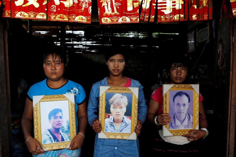 Women pose while holding portraits of their killed relatives Aik Sai, Aik Maung and Aik Lort after their bodies were found in a grave last June at Mong Yaw village in Lashio